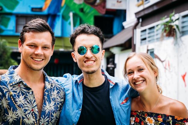 Três jovens de diferentes etnias se abraçando pelas costas no meio de uma rua com fachadas coloridas decoradas com arte de rua