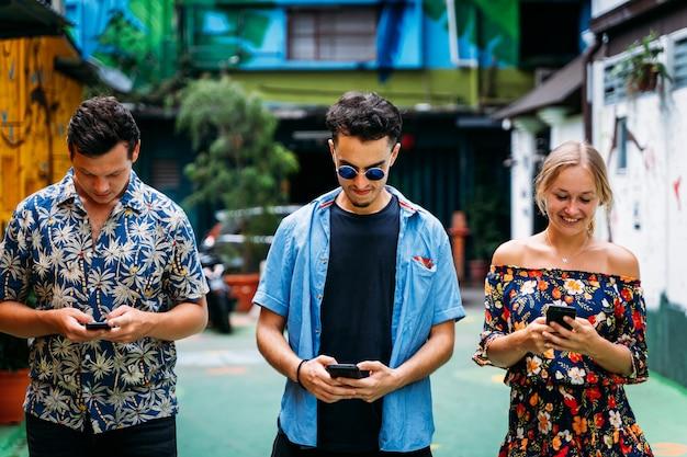 Três jovens de diferentes etnias usando um celular no meio de uma rua com fachadas coloridas e arte de rua