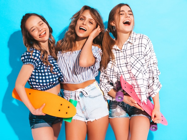 Três jovens elegantes sexy sorridentes meninas bonitas com skates centavo coloridos. mulheres em roupas de camisa quadriculada verão em óculos de sol. modelos positivos se divertindo