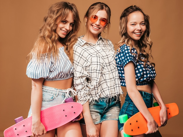 Três jovens elegantes sorridentes meninas bonitas com skates centavo colorido. mulher no verão camisa quadriculada roupas posando. modelos positivos se divertindo