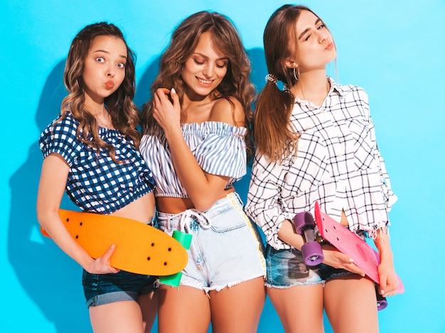 Três jovens elegantes sorridentes meninas bonitas com skates centavo colorido. mulheres em roupas de camisa quadriculada verão posando. modelos positivos se divertindo