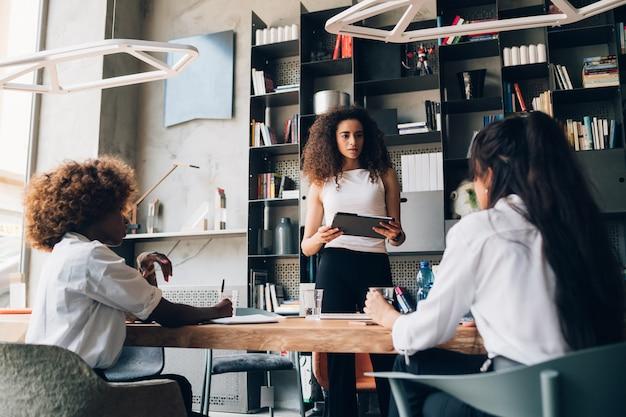 Três jovens empresárias multiculturais falando sobre projeto no escritório de coworking