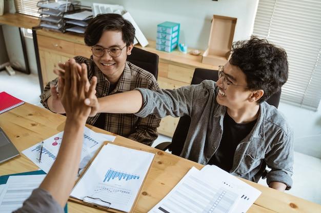 Três jovens empresários asiáticos trabalham juntos de acordo no planejamento com um gesto de união