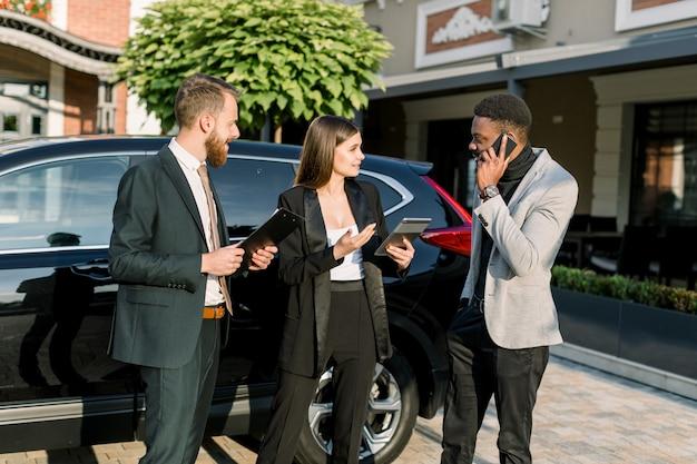 Três jovens empresários multiétnicos discutem algo ao ar livre perto de carro preto. mulheres caucasianas, segura, tablete, homem africano, falando telefone, e, caucasiano, homem, segurando, contratos negócio