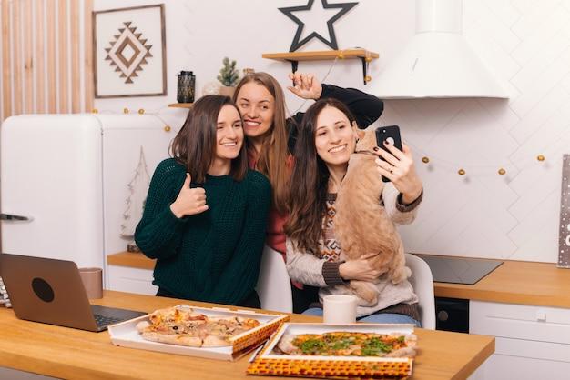 Três jovens estão comemorando o natal com pizza em casa na cozinha.