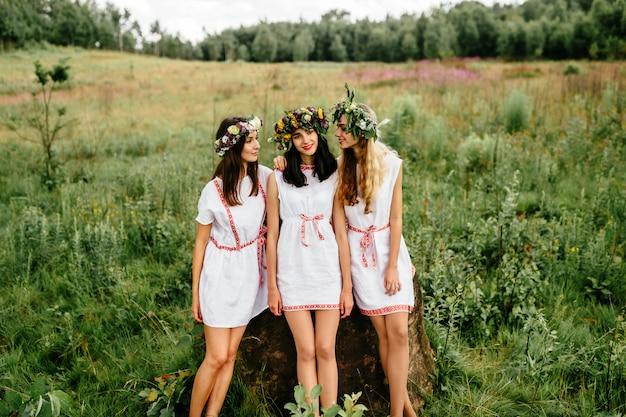 Três jovens étnicas em vestidos brancos, posando no campo.