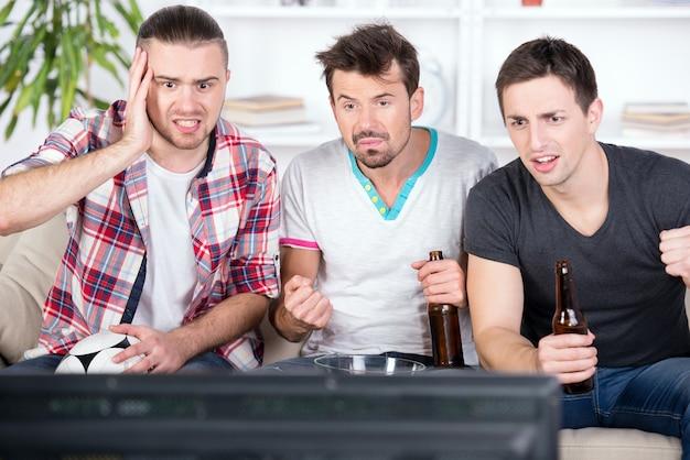 Três jovens fãs de futebol estão torcendo jogo de futebol.
