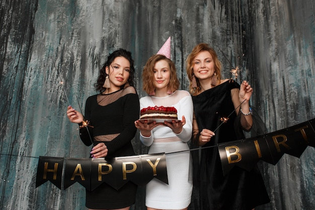 Três jovens garotas bonitas comemorar aniversário segurando bolo e estrelinhas