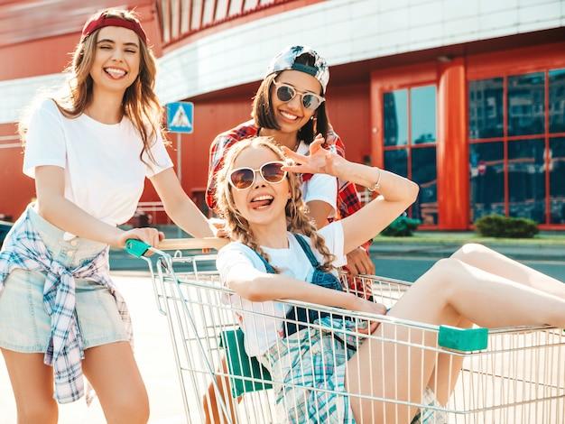 Três jovens garotas bonitas se divertindo no carrinho de compras