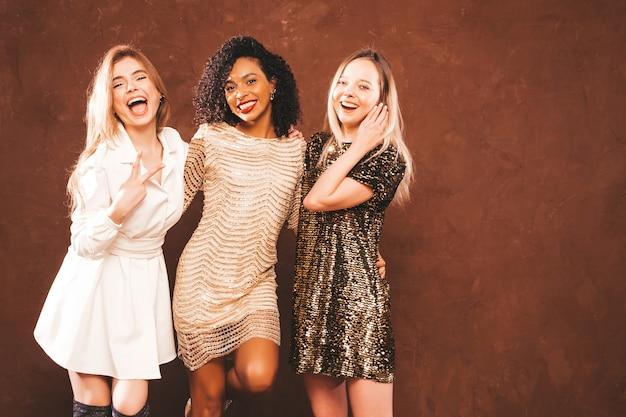 Três jovens internacionais lindas mulheres morenas em um vestido brilhante de verão na moda.