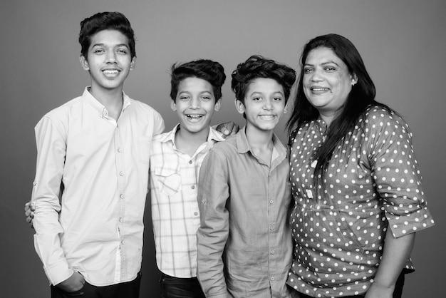Três jovens irmãos indianos e sua mãe juntos contra uma parede cinza em preto e branco