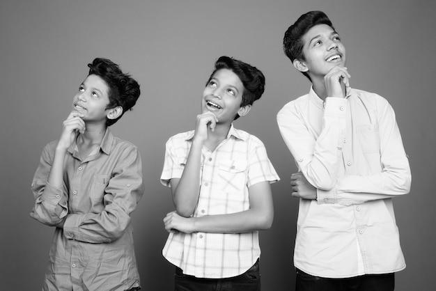 Três jovens irmãos indianos juntos contra uma parede cinza em preto e branco
