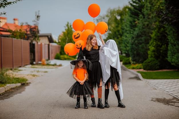 Três jovens irmãs em trajes de halloween, como fantasma e bruxas engraçadas posando na rua com balões de abóbora, conceito de férias.