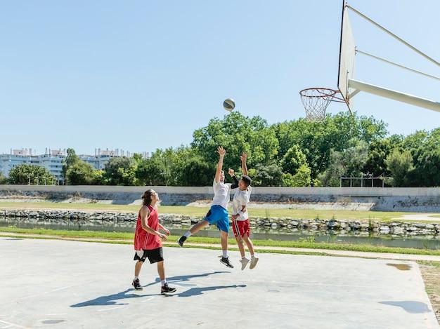 Três jovens jogadores na quadra de basquete