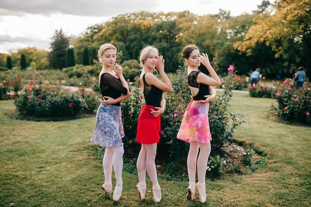 Três jovens lindas bailarinas em collants e saias coloridas posando com graça no parque de verão.