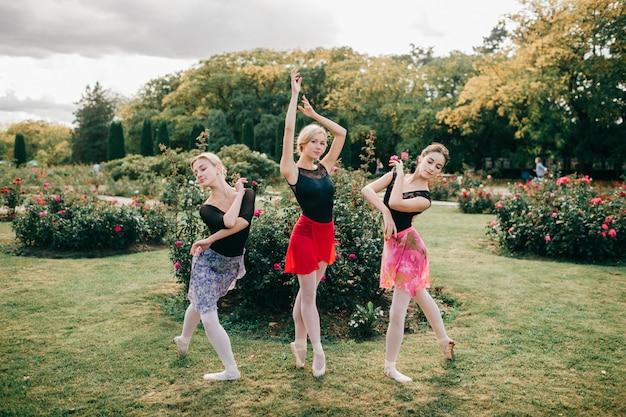Três jovens lindas bailarinas posando com graça no parque de verão.
