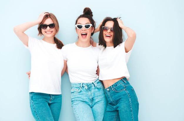 Três jovens lindas e sorridentes mulheres hippie no mesmo verão, camiseta branca e roupas jeans