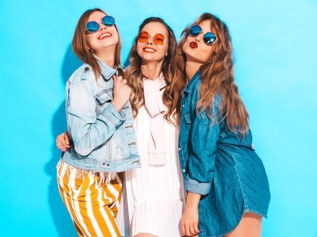Três jovens lindas meninas sorridentes em roupas de jeans casual de verão na moda. mulheres sexy despreocupadas posando. modelos positivos em óculos de sol