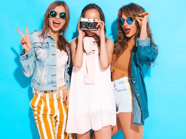 Três jovens lindas meninas sorridentes em vestidos casuais de verão na moda e em óculos de sol. mulheres sexy despreocupadas posando. tirando fotos na câmera retro