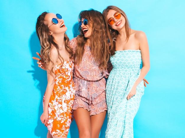 Três jovens lindas meninas sorridentes em vestidos casuais de verão na moda e em óculos de sol. mulheres sexy despreocupadas posando.