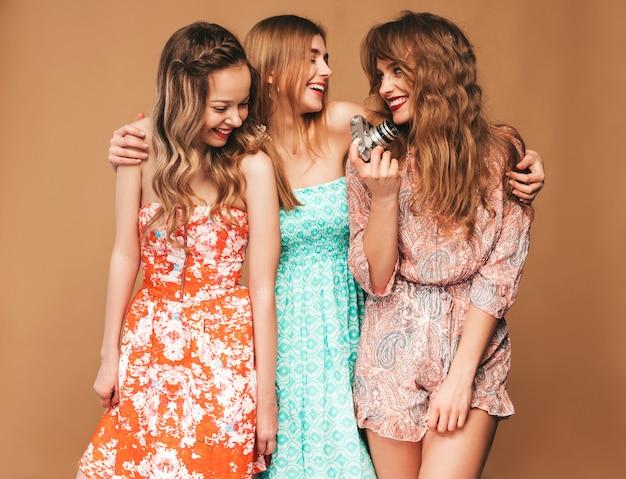 Três jovens lindas meninas sorridentes em vestidos casuais de verão na moda. mulheres sexy despreocupadas posando. tirando fotos na câmera retro