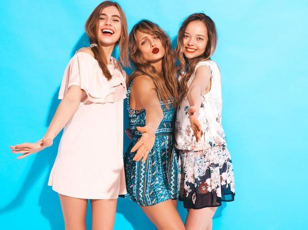 Três jovens lindas meninas sorridentes em vestidos casuais de verão na moda. mulheres sexy despreocupadas posando.