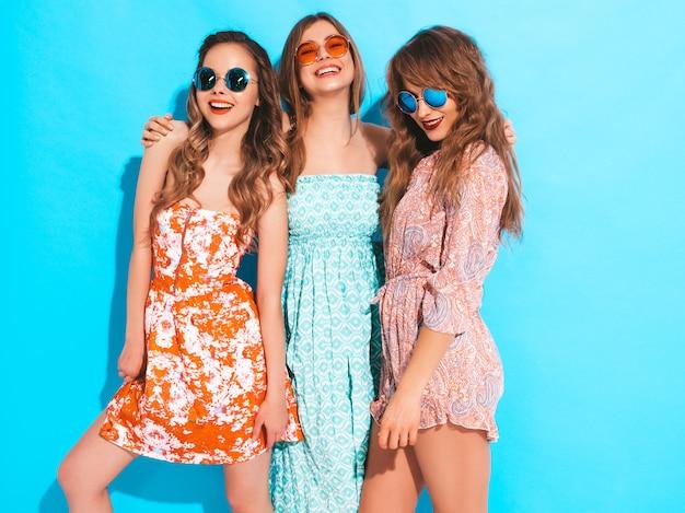 Três jovens lindas meninas sorridentes em vestidos coloridos na moda verão. mulheres despreocupadas sexy em óculos de sol.