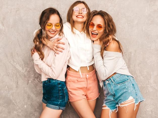 Três jovens lindas meninas sorridentes no verão na moda esporte roupas. mulheres sexy despreocupadas posando. modelos positivos em óculos de sol redondos se divertindo. abraçando