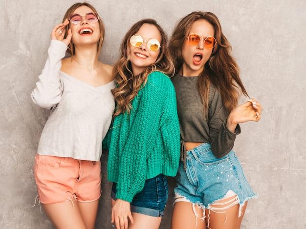 Três jovens lindas sorrindo lindas garotas em roupas da moda no verão. mulheres sexy despreocupadas posando. modelos positivos se divertindo em óculos de sol redondos