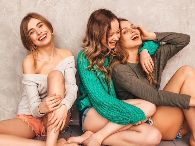 Três jovens lindas sorrindo lindas garotas em roupas da moda no verão. mulheres sexy despreocupadas posando. modelos positivos se divertindo. sentado no chão. abraçando