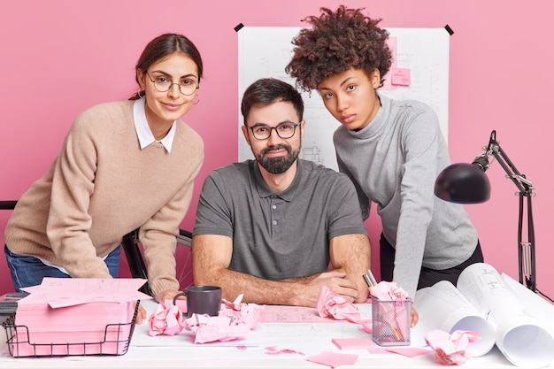 Três jovens motivados discutem um plano de cooperação em poses de projetos arquitetônicos comuns em um escritório de coworking moderno e colaboram para fazer pesquisas