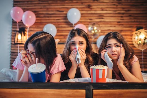 Três jovens mulheres deitadas na cama na sala festiva. eles assistem filmes e choram. meninas segurar guardanapos brancos nas mãos.