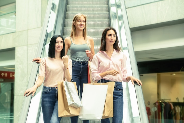 Três jovens mulheres em compras no shopping