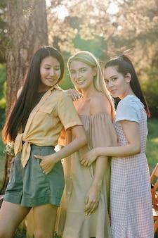 Três jovens mulheres felizes em roupas casuais, perto uma da outra enquanto passam um tempo no parque num dia de verão