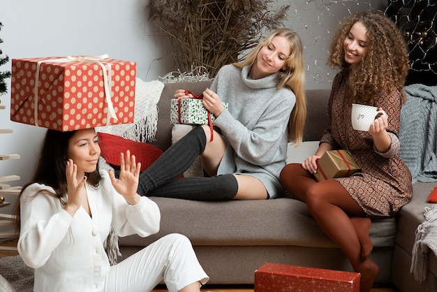 Três jovens mulheres felizes se divertem embalando presentes de natal em um ambiente caseiro aconchegante
