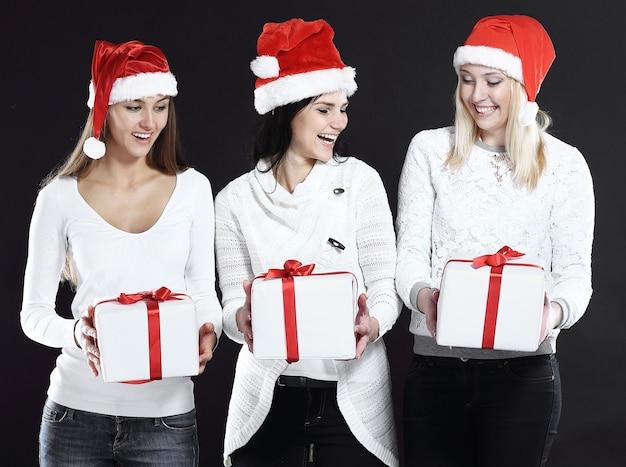 Três jovens mulheres na fantasia de papai noel com shopping.photo de natal com espaço de cópia.