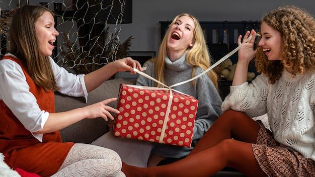 Três jovens mulheres sentadas no sofá e se divertindo desembrulhando os presentes de natal em casa
