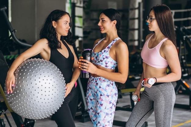 Três jovens mulheres treinando na academia