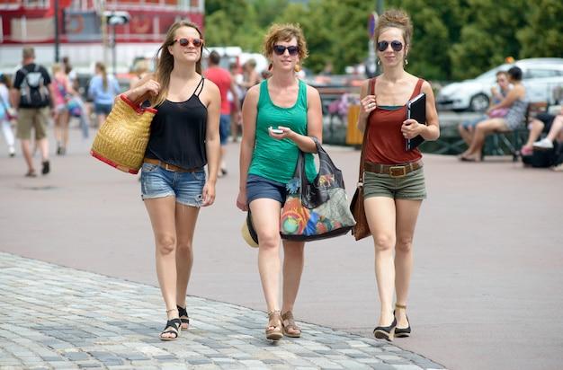 Três jovens mulheres vão às compras