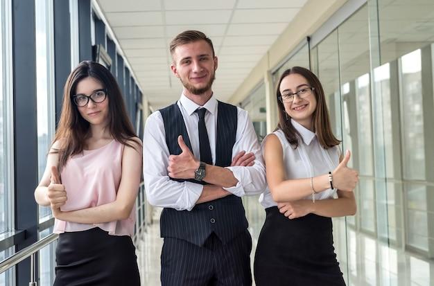 Três jovens parceiros de negócios felizes discutindo contrato ou relatório em pé no corredor do escritório.