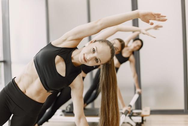 Três jovens se encaixam mulheres treinando na academia. mulheres vestindo roupas esportivas pretas. meninas brancas, exercitando-se com equipamento.