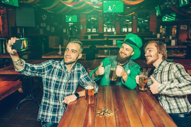 Três jovens sentam à mesa no pub e tomam selfie. eles posam e sorriem. cara no meio espera telefone.
