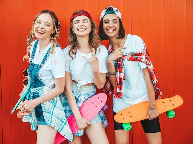 Três jovens sorridentes meninas bonitas com skates centavo colorido.