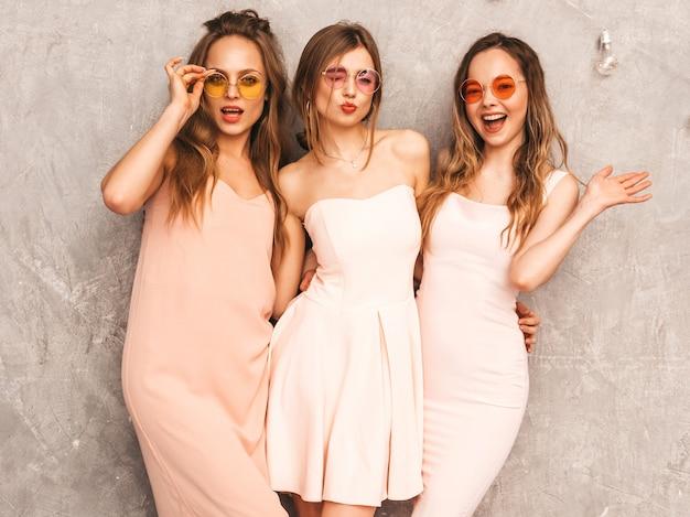 Três jovens sorridentes meninas bonitas na moda verão luz rosa vestidos. mulheres sexy despreocupadas posando. modelos positivos em óculos de sol redondos se divertindo
