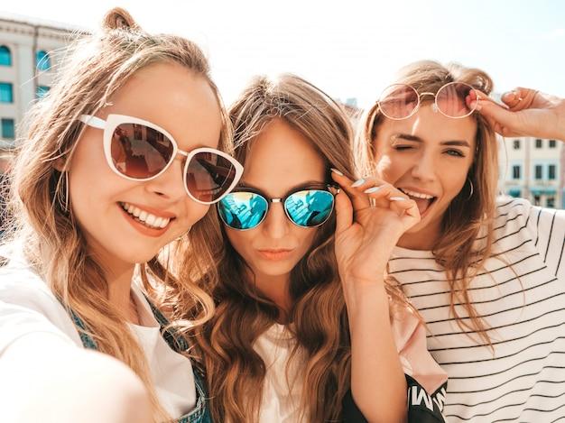 Três jovens sorrindo hipster mulheres em roupas de verão. garotas tirando fotos de auto-retrato de selfie em smartphone. modelos posando na rua. feminino mostrando emoções de rosto positivo