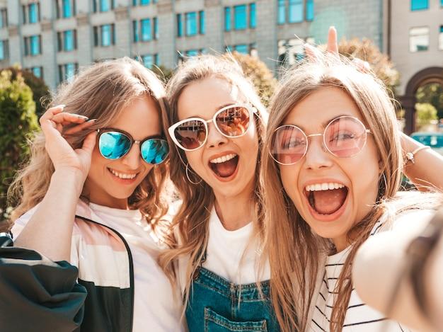 Três jovens sorrindo hipster mulheres em roupas de verão. meninas tirando fotos de auto-retrato de selfie em smartphone. modelos posando na rua. feminino mostrando emoções de rosto positivo em óculos de sol