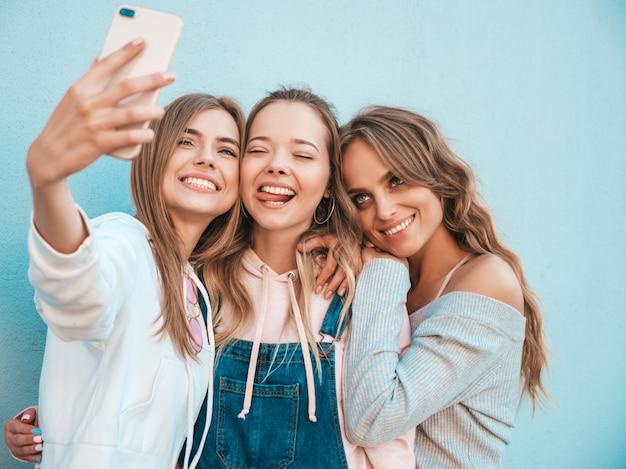 Três jovens sorrindo hipster mulheres em roupas de verão. meninas tirando fotos de auto-retrato de selfie em smartphone. modelos posando na rua perto da parede. feminino mostrando emoções de rosto positivo.