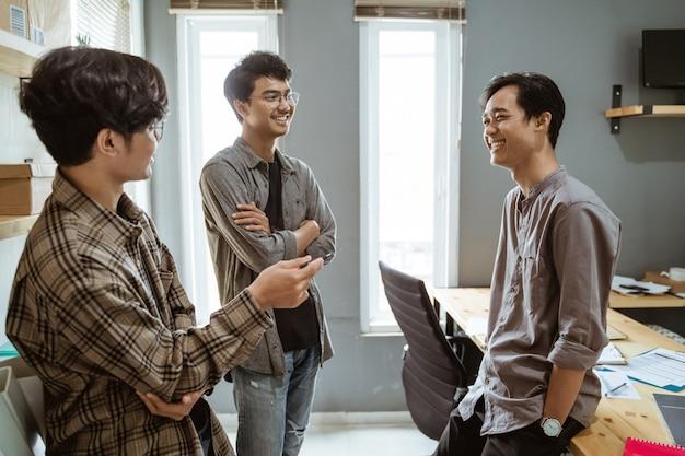 Três jovens trabalhadores asiáticos conversando sobre seu produto