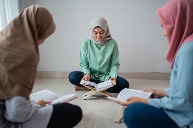 Três jovens vestindo hijabs, lendo o livro sagrado do corão