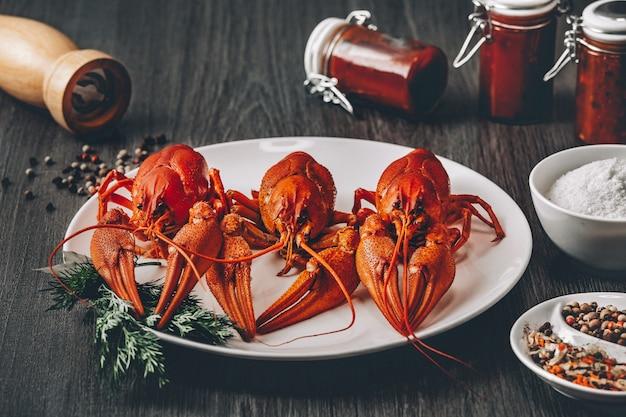 Três lagostins cozidos em um prato branco com potes de molho de sal de ervas verdes e grãos de pimenta